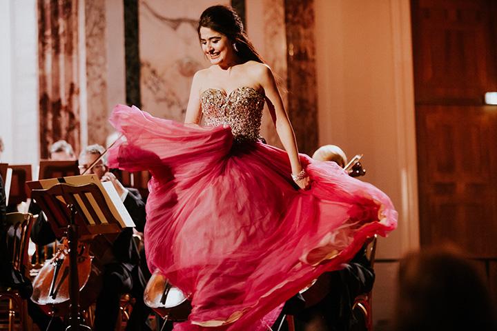 Сопрано Венского оркестра Хофбург танцует в розовом платье на сцене для принцессы Цардаса