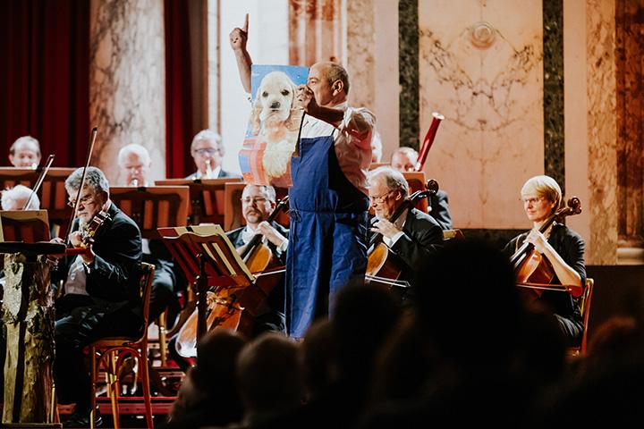 классический рождественский концерт - барабанщик оркестра держит картину с собакой